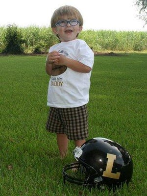 Thomas Moore, son of Leesville High School head football coach Tommy Moore, poses with a football helmet.