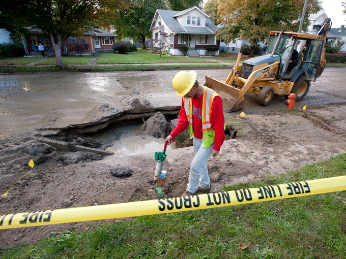 Vince Crabtree of US Infrastructure Corporation pains a line after locating underground utility pipes near the site of a caved-in street in the 1700 block of S. 3rd Street , damaged when a 12-inch water main broke. Louisville Water Company shut off the water and set about repairing the damage. Oct. 23, 2013