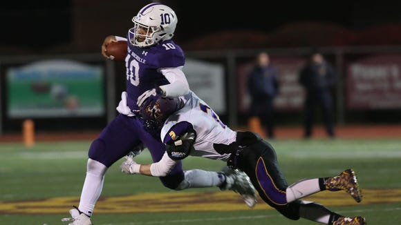 New Rochelle quarterback Jonathan Saddler (10) tries to break away from Troy's Nick Pastore (2) on a first half run, during the state Class AA semifinal football game at Dietz Stadium in Kingston, N.Y. Nov. 19, 2016