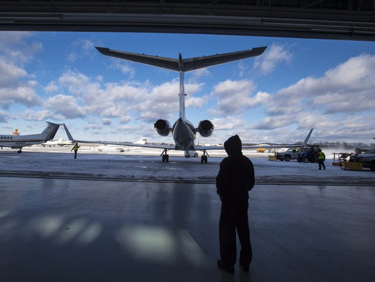 A jet is towed out of a hanger at Heritage Aviation
