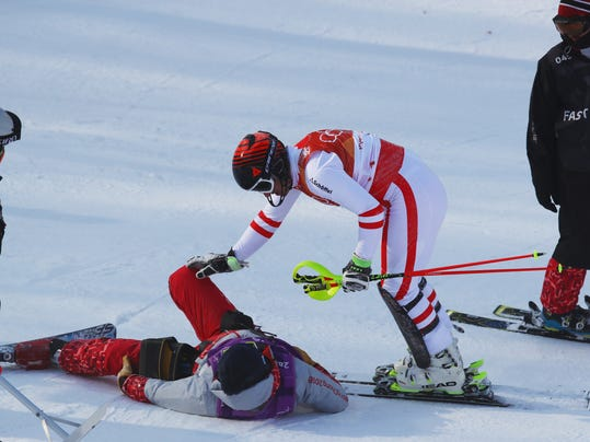 Austria's Matthias Mayer checks on an official after colliding with him after crashing in the slalom portion of the men's combined at the 2018 Winter Olympics in Jeongseon, South Korea, Tuesday, Feb. 13, 2018. (AP Photo/Alessandro Trovati)