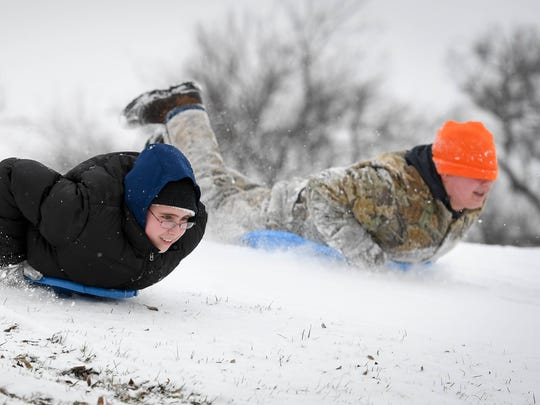 Reid Blaine. left, and Dalton Hinkle race each other down a hill on the Henderson Municipal Golf course as the first measurable snow hit the area closing schools Thursday, January 5, 2017.