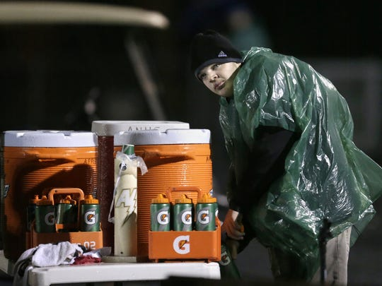 Will Carroll, an Appleton North High School football manager, fills up water bottles during North's game last week against Appleton West.