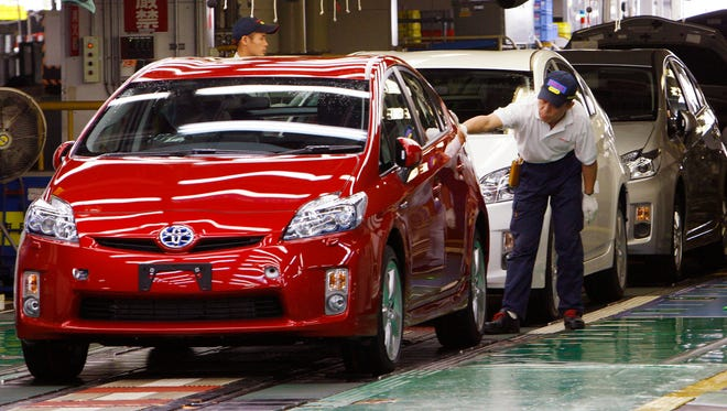 A  Toyota worker gives the final examination on an newly assembled Prius at Toyota Tsutsumi Plant in Toyota, central Japan, in this 2009 file photo
