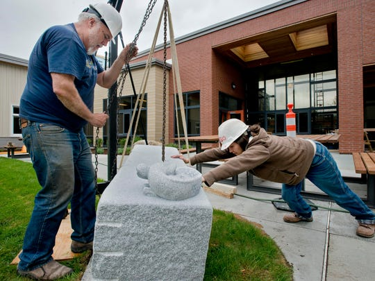 Granite sculptors Chris Miller and Heather Milne work to install one of their pieces at the new Vermont Psychiatric Care Hospital in Berlin on Friday. They are two of four local sculptors to make pieces for the new facility.