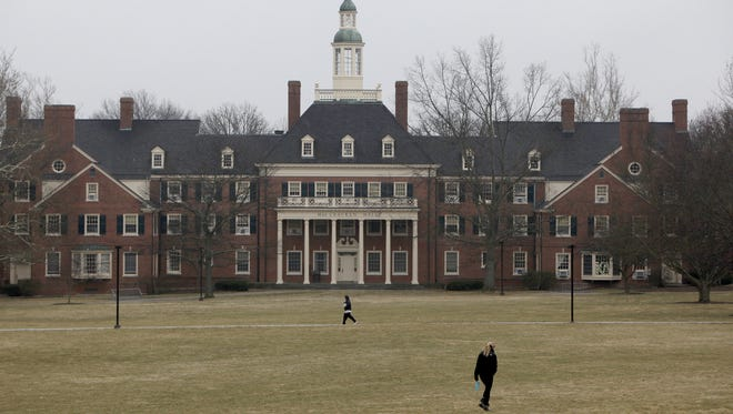 Students walk across the lawn in front of MacCracken Hall at Miami University, in Oxford, Ohio.