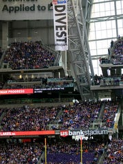 FILE -In this Jan. 1, 2017, file photo, protesters against the Dakota Access Pipeline rappel from the catwalk after placing a banner in U.S. Bank Stadium during an NFL football game between the Minnesota Vikings and Chicago Bears in Minneapolis. The front lines of the battle against the $3.8 billion Dakota Access pipeline are shifting away from the dwindling encampment in North Dakota.