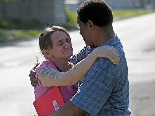 Eddie Howell comforts a neighbor saddened by the fire at his home at 301 West Fourth Street early Friday morning.