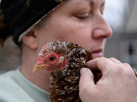 Debbie Melton embraces Ms. Frizzle, one of her pet chickens, while taking a break from cleaning out her flooded basement Friday afternoon, March 9, 2018. Melton considers her chickens to be therapeutic pets and was extremely upset to lose 15 while dealing with the flood.