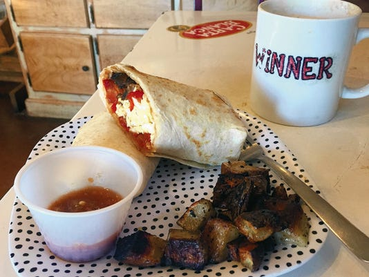 A breakfast wrap can be customized by each customer, this one includes tomatoes, mushrooms, and bell peppers with a side of papas (7) and was served with a chai tea latte (3.50).