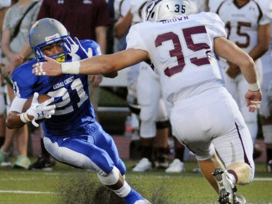 Cedar Crest's Iziah Trimble looks to stiff arm the Barons' Nick Brown during their game Friday at Earl Boltz Stadium.