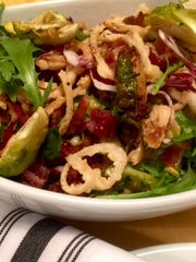 Nook sources  local ingredients for seasonal salads like this one with chopped kale, arugula, shaved Brussels sprouts, cranberry, parmesan, fried shallots and candied bacon in tahini maple dressing.