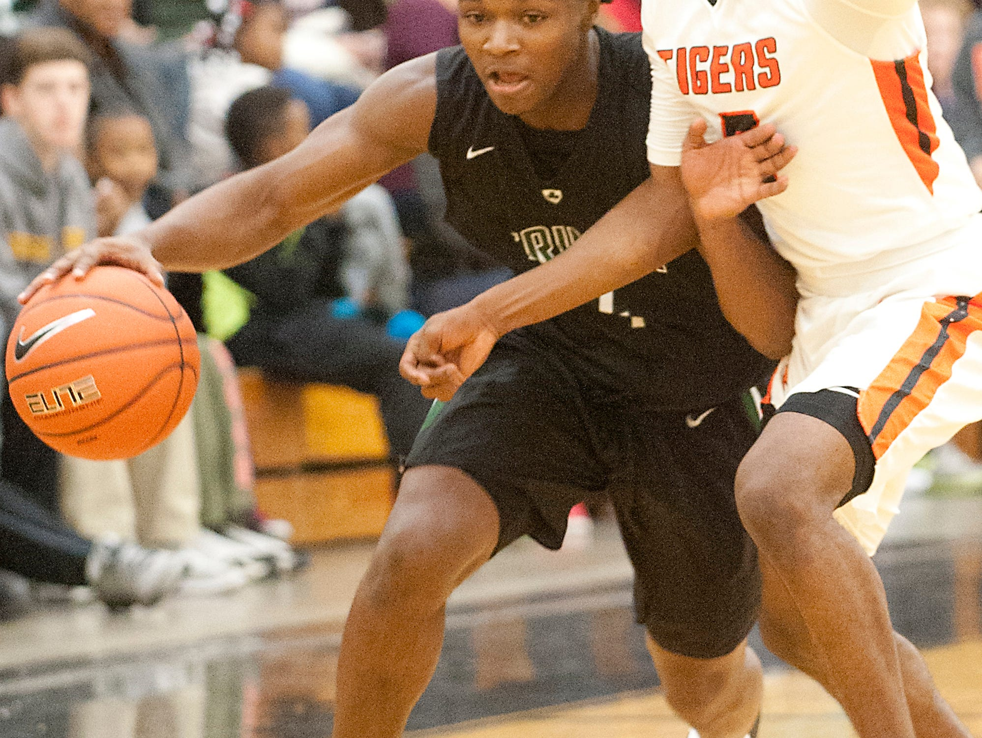 Trinity guard Damon McClain turns the corner as Fern Creek guard Anthony Wales keeps on the pressure. 10 December 2016