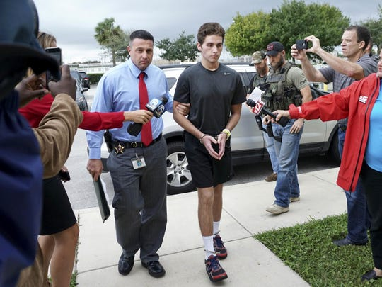 Austin Harrouff is transported by detectives to the Martin County Jail after being released from St. Mary's Hospital. Deputies say the college student bit a man's face after stabbing him and his wife to death outside their Florida home.