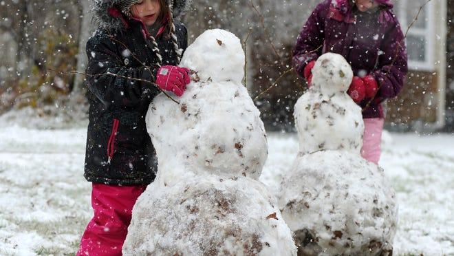 Amellia Cimino, left, and Jasmine Charbarneau build snowmen in 2011 in Merrill.