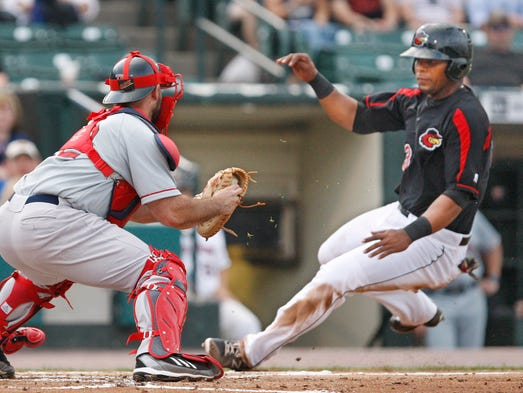 Rochester's Deibinson Romero is tagged out at home by Pawtucket catcher Dan Butler as he tries to score from third on an infield grounder by teammate Josmil Pinto in the first inning of their game Tuesday, June 17, 2014 at Frontier Field.