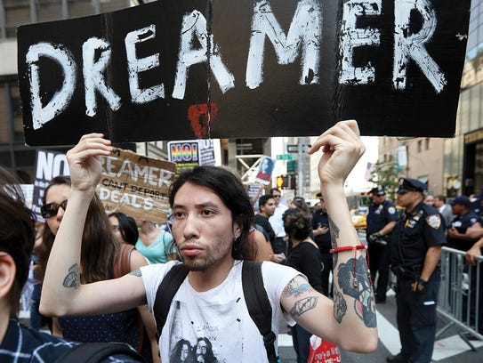 Joban Rodriguez, 27, holds a sign as he walks past