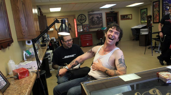 """David Zollo laughs as he cracks a joke with Ray """"Stingray"""" Parrish at Nix Rue Tattoo in North Liberty on Thursday, Sept. 18."""