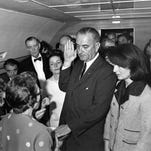 With Jacqueline Kennedy at his side, Lyndon B. Johnson is sworn in as the nation's 36th president aboard Air Force One at Dallas Love field on Nov. 22, 1963.