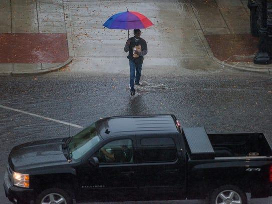 Pedestrians make their way through the downpour of