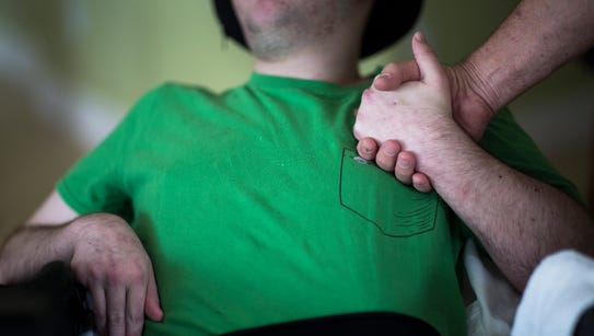Mitchell Reidy, 19, holds his dad's hand while sitting