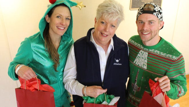 Everyday Hero Debbie Ford, center, is flanked by two elves (McMurry University women's basketball coach Brittany Densman-Roes and her assistant, Will Sherman) at a holiday luncheon at which each received a gift from Santa. Ford is the executive administrative assistant for McMurry's athletics department.