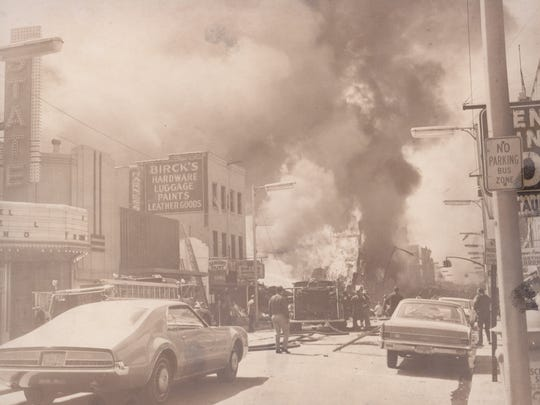 Flames and smoke rise from the intersection of Sixth