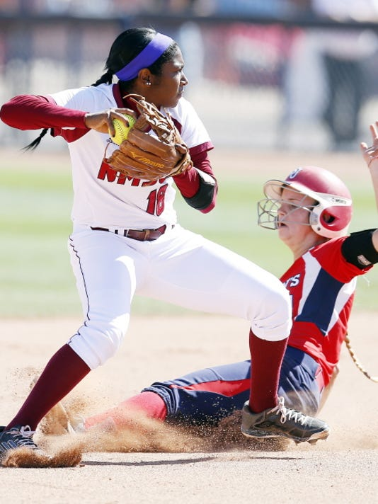 New Mexico State infielder Rachel Rodriguez (18) gets the force-out on St. Johns' Hannah Anderson in the first inning during an NCAA college softball tournament regional game on Saturday in Tucson, Ariz. (AP Photo/Rick Scuteri)