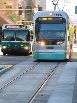 A city bus and light rail train travel on Central Avenue in downtown Phoenix.