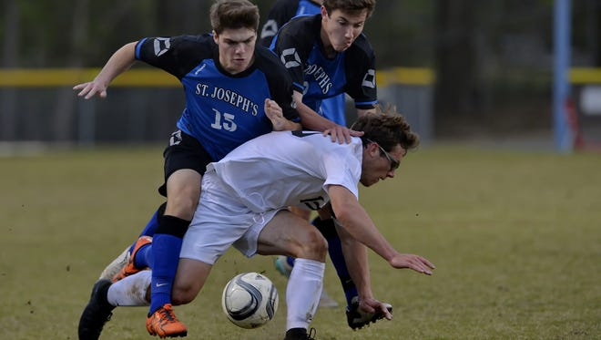St. Joseph's teammates Travis Griffin (15) and Drew Luzzatti collide with Christ Church's Lee Cox while battling for possession during the visiting Knights' 1-0 win over the Cavaliers at Carson Stadium Monday night.