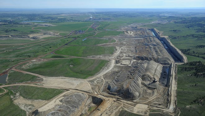 This photo taken May 25, 2013, shows an aerial view of Colstrip power plants 1,2,3 & 4 and the Westmoreland coal mines near Colstrip, Mont. U.S. officials have approved a 60-million ton expansion of a southeastern Montana coal mine that serves one of the largest power plants in the western United States, Interior Secretary Ryan Zinke's office said Friday, Dec. 22, 2017. The approval will extend the life of Westmoreland Coal Company's Rosebud Mine by 19 years and adds 10.5 square miles (27 square kilometers) to the 40-square-mile (104-square kilometer) strip mine, Zinke spokeswoman Heather Swift said. (Larry Mayer/The Billings Gazette via AP)