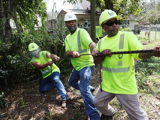 A crew from Wright Tree Service helps clear power lines