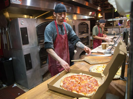 Chris Rojo boxes a pizza for a take-out order Friday at the Three Rivers Pizzeria in Farmington.
