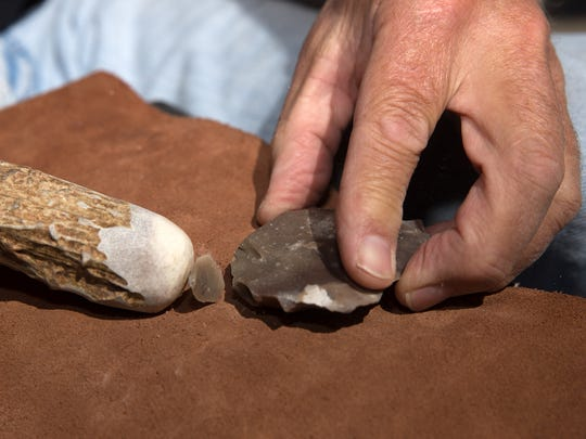 Bruce Burks demonstrates flintknapping by using an antler to chip off a flake of obsidian to create an arrowhead or a blade on Thursday during a workshop at the Bonnie Dallas Senior Center in Farmington.