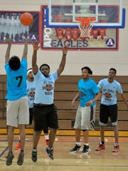 Members of the Originals, in darker blue, play against the Hall of Fames Saturday during the St. Cloud Somali Youth Organization Basketball Tournament at Apollo High School.
