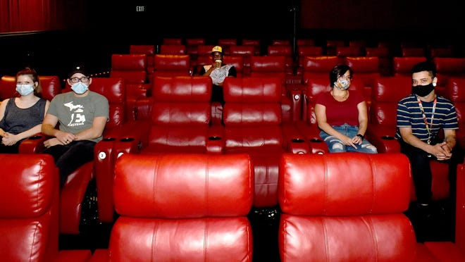 Employees at Phoenix Theatres in Monroe show how seating for social distancing will take place in cinemas.