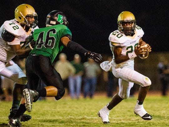Acadiana quarterback Myles Hutchinson (20) rolls out