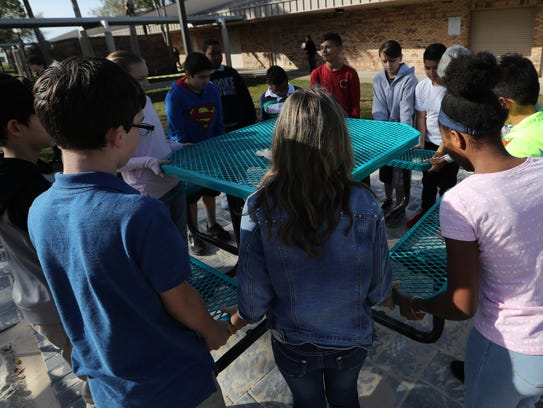 """Students of Al Piotter's STEM-scaping class at Trafalgar Middle School in Cape Coral, move into place one of the benches that will be part of an outdoor area of the campus that they refer to as """"Trafalgar Square"""". The area will be for mixed use purposes and was developed primarily with the assistance of the students."""