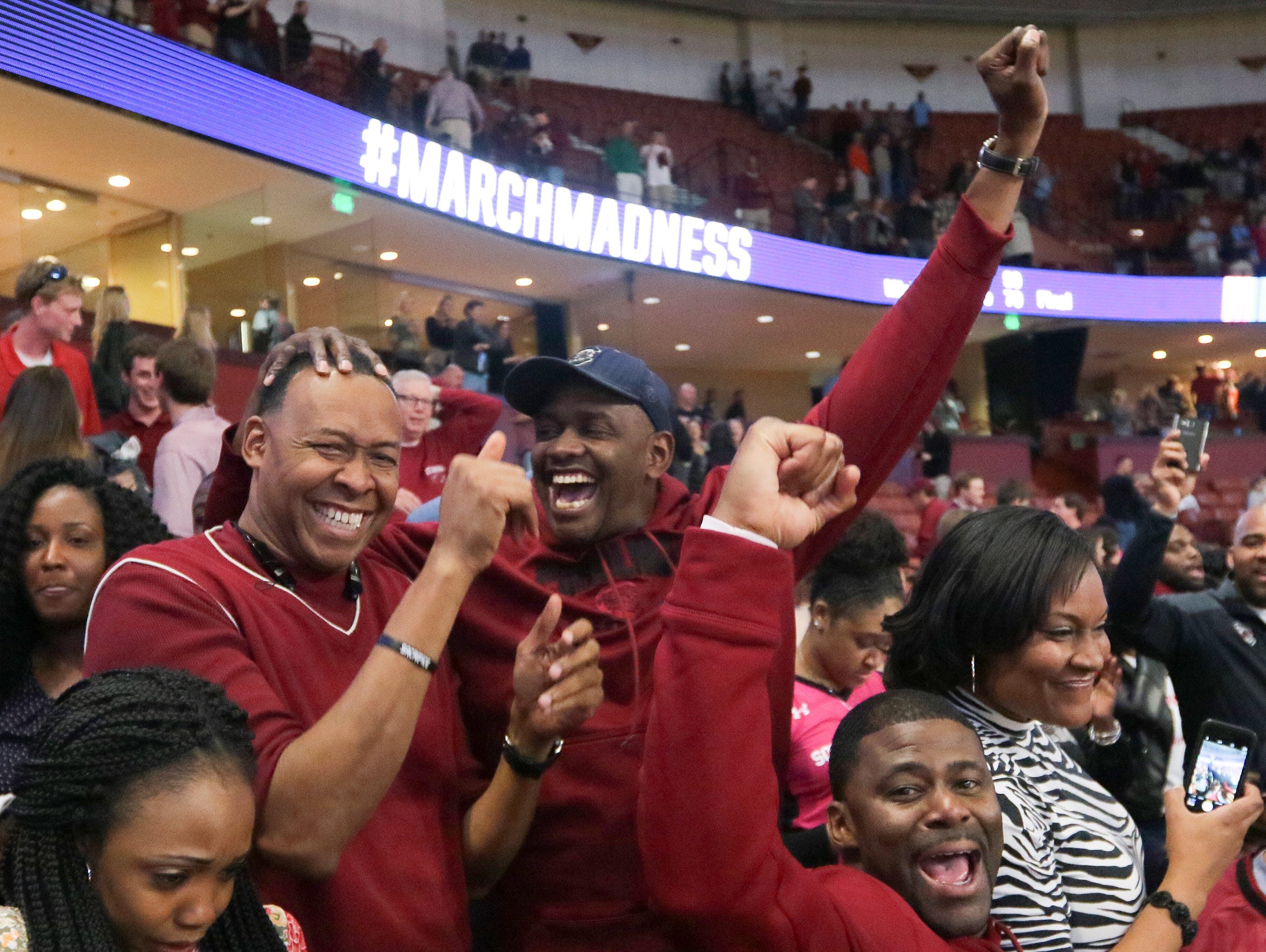 Perry Dozier, left, Terry Dozier, and B.J. McKie, former South Carolina players, cheer after an 88-81 win over Duke during the 2nd round of the NCAA Tournament at Bon Secours Wellness Arena in downtown Greenville on Sunday, March 19, 2017.