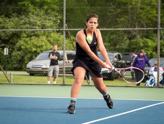 Cecile Rousseau hits the ball during her doubles match