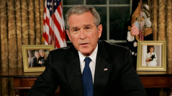 President George W. Bush pauses in the Oval Office