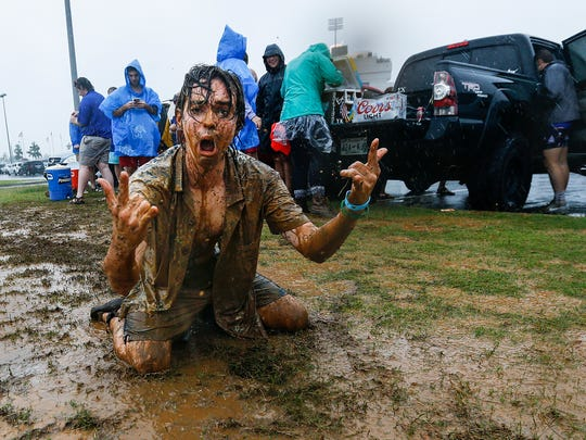 University of Memphis student Matthew Barczak (middle) celebrates sliding in a mud puddles, as heavy rains pour down outside the Liberty Bowl Memorial Stadium before the Tigers first football game of the season against Louisiana-Monroe, Thursday evening.