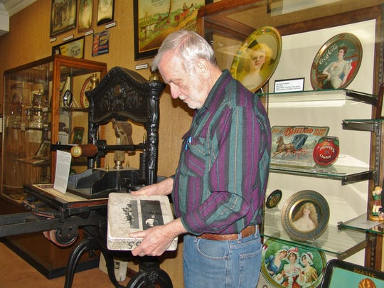 Joe Kreitzer looks at a litho stone used in the printing process of the early days of advertising art in Coshocton.
