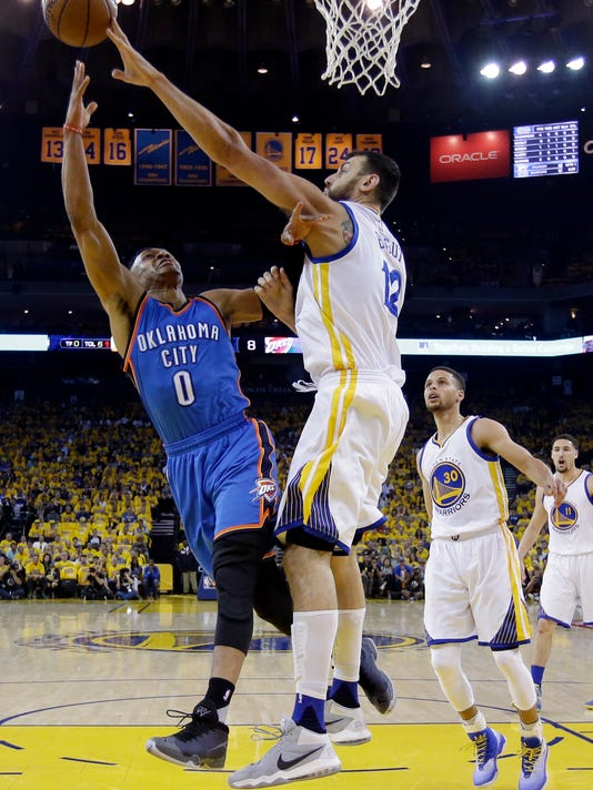 Oklahoma City Thunder's Russell Westbrook (0) drives to the basket as Golden State Warriors' Andrew Bogut (12) defends during the first half in Game 1 of the NBA basketball Western Conference finals Monday, May 16, 2016, in Oakland, Calif. (AP Photo/Marcio Jose Sanchez)