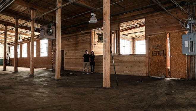 Tony and Caroline Galzin stand inside the space that will become their new restaurant, Nicky's Coal Fired.