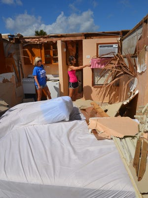 Amy Newsome and Angie Breadwell, daughters of the owner of Sea Aire Motel in Cocoa Beach, survey the damage to the motel. The oceanfront building lost its roof, destroying seven rooms.