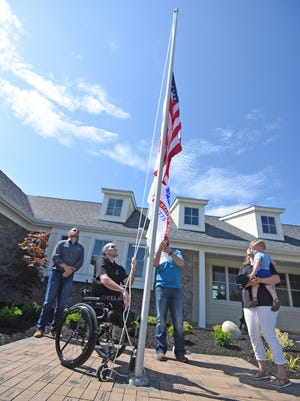 "Nick Vogt raises the flag Friday morning as he and wife Lauren and son Nathan receive their ""forever home"" from the Gary Sinise Foundation."