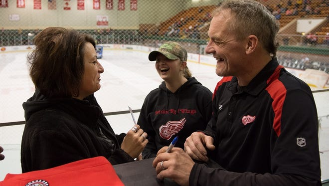 Darren McCarty enteracts with a fan Thursday night at McMorran Arena.