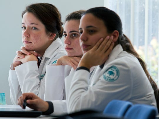 From left, nursing students Samantha Link, Danielle Gorman and Marla Herrera listen attentively during a classroom discussion at Nova Southeatern University.