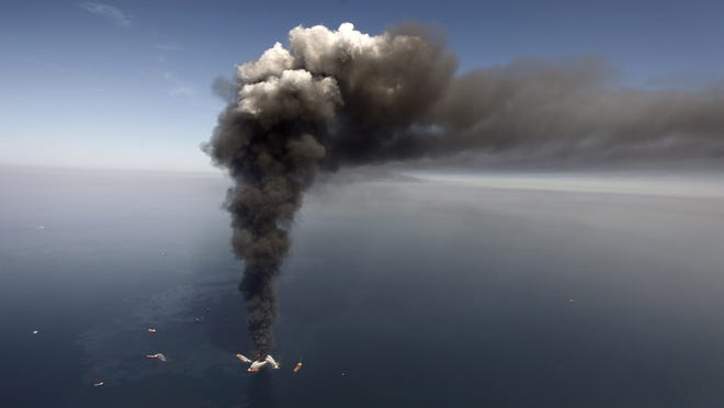 In this April 2010 file photo, oil can be seen in the Gulf of Mexico, more than 50 miles southeast of Louisiana as a large plume of smoke rises from fires on BP's Deepwater Horizon offshore oil rig.